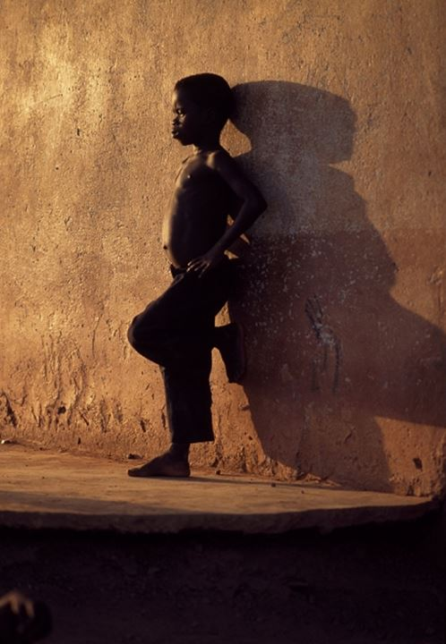 Side profile of a boy leaning against a wall, Ghana