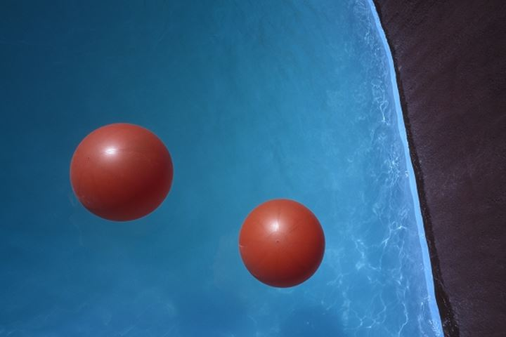 Two red balls over water