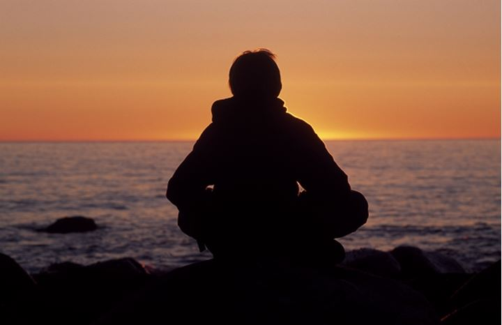 Silhouette of a man meditating on a seashore