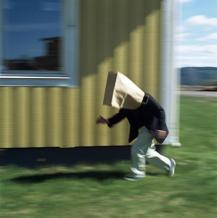 Side profile of a boy running with his face covered with a paper bag