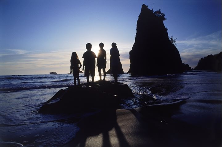 Four kids standing on rock at sunset in Olympic National Park