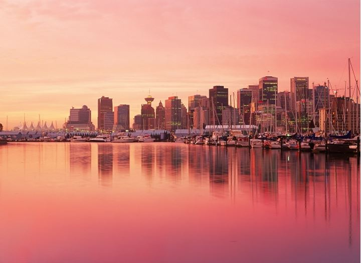 Mirror images of Vancouver skyline on harbor waters from Stanley Park at dawn