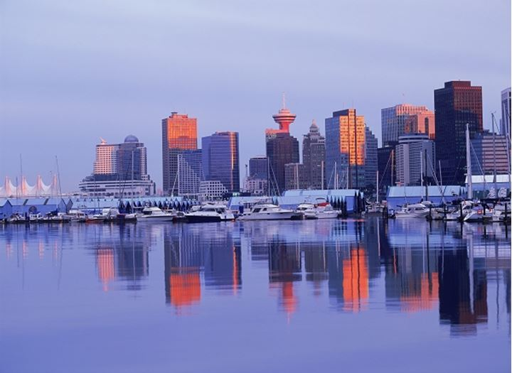 Mirror images of Vancouver skyline on harbor waters from Stanley Park at dusk