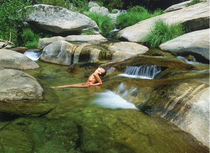 Naked woman relaxing in mountain stream in Spain
