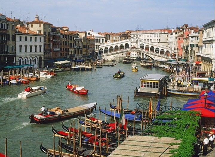 Boat traffic on Grand Canal with Rialto Bridge in Venice