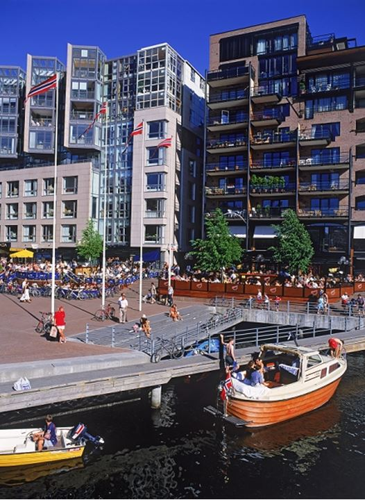 Seaside restaurants and canals with passing boats at Aker Pier in Oslo