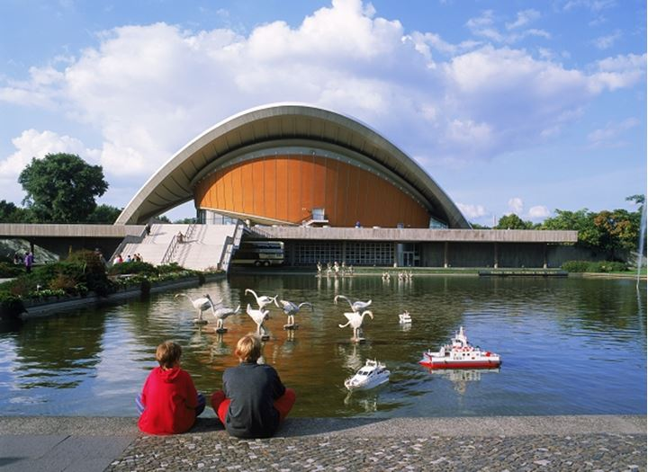 Boys with remote controlled boats on pond at Kongresshalle in Berlin