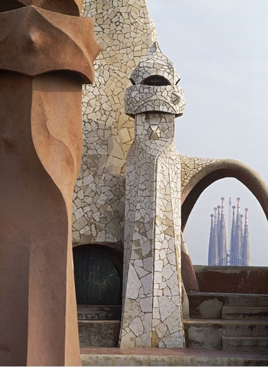 Casa Mila or La Pedrera by Antoni Gaudi with Sagrada Familia beyond in Barcelona