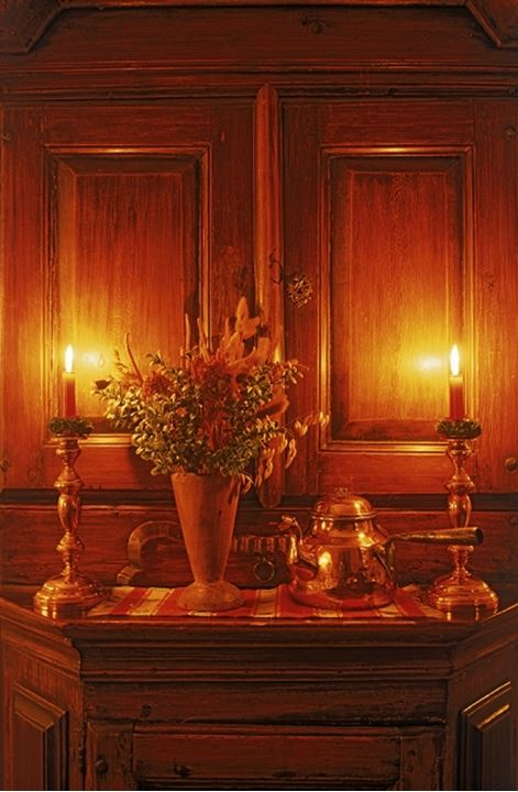 Candles and brass coffee pot on antique wooden bureau