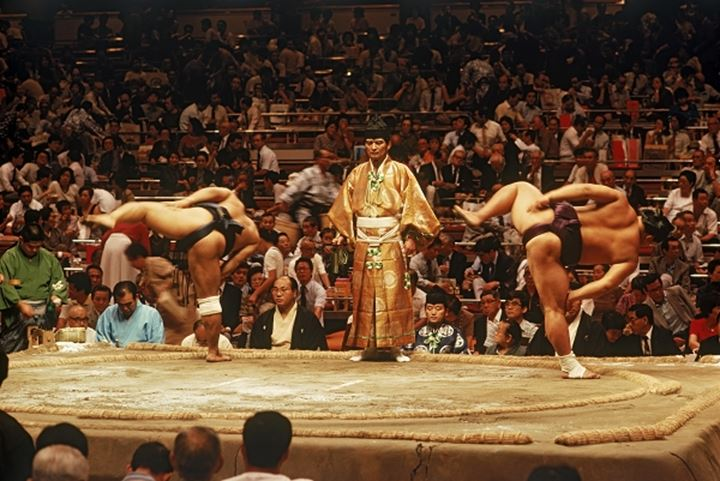 Sumo wrestlers pre fight ceremony of leg stamping in ring or dohyo