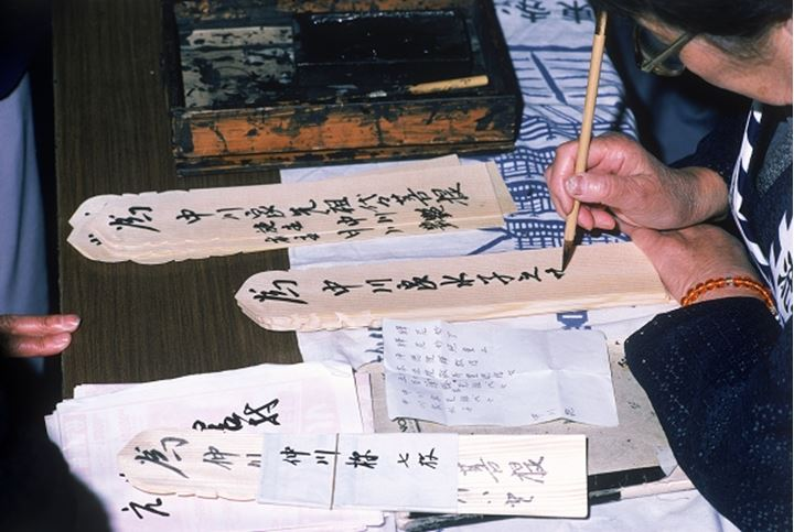 Writing prayers on toba sticks outside Buddhist temple in Japan