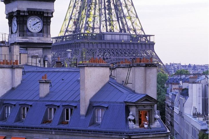 Woman in apartment with coffee cup near Eiffel Tower