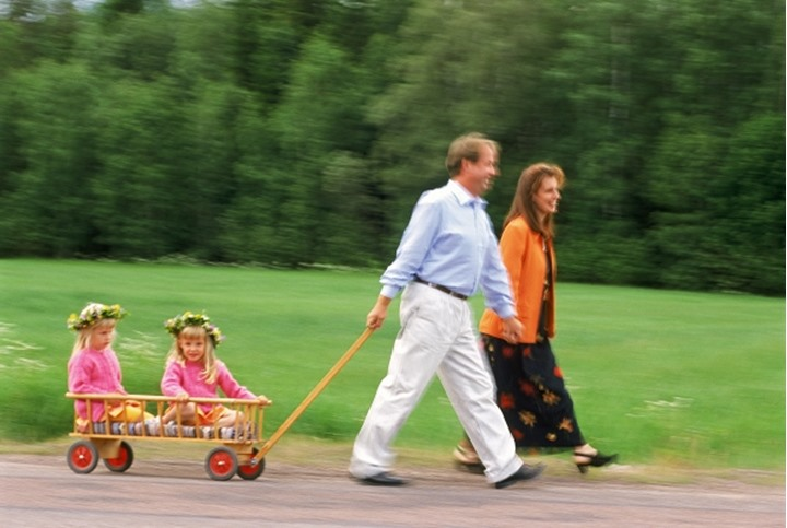 Parents on country road pulling two daughters in little wagon