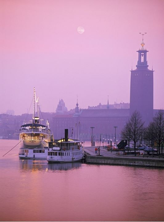 Steamboat and ferryboat moored at Riddharholmen in Stockholm with City Hall silhouetted under full moon at sunrise
