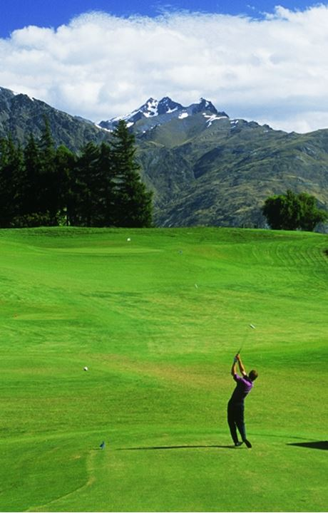 Golfer hitting off Millbrook Golf Course fairway in Southern Alps of New Zealand