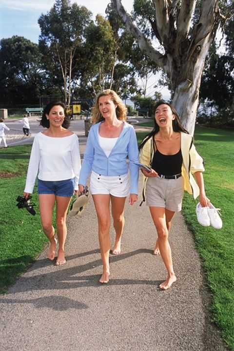Three women of ethnic mix walking barefoot on park pathway
