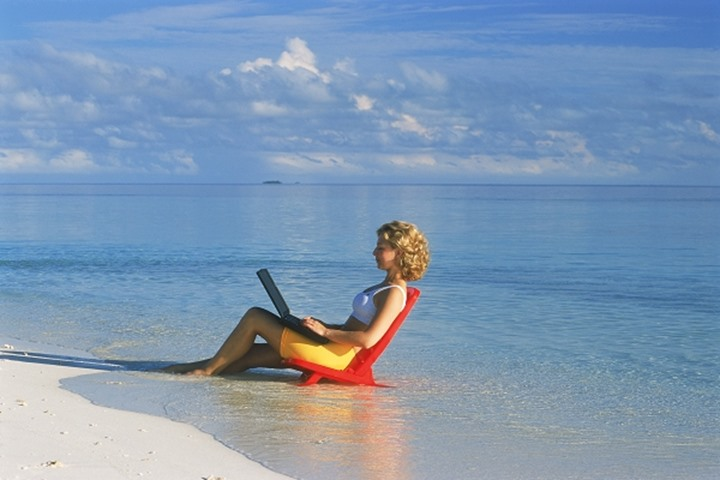 Woman on sandy shore with laptop during working holiday