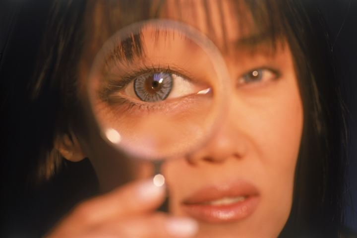 Asian woman looking through magnifying glass