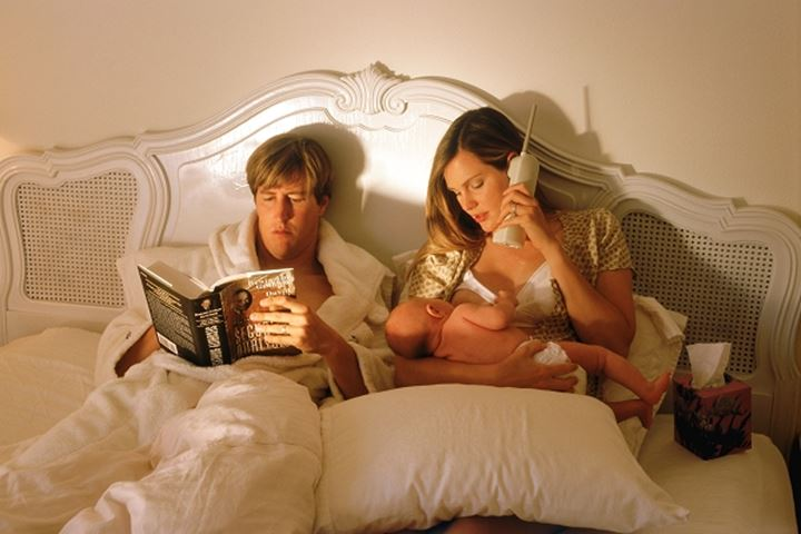 Dad reading and Mom talking on telephone and holding baby in bed
