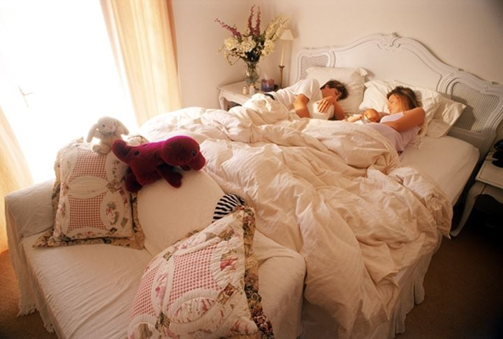 Family of three sleeping in bedroom filling with morning light