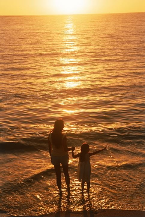 Mother and daughter holding hands on beach in sunset light