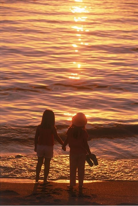 Two girls on beach in sunset light