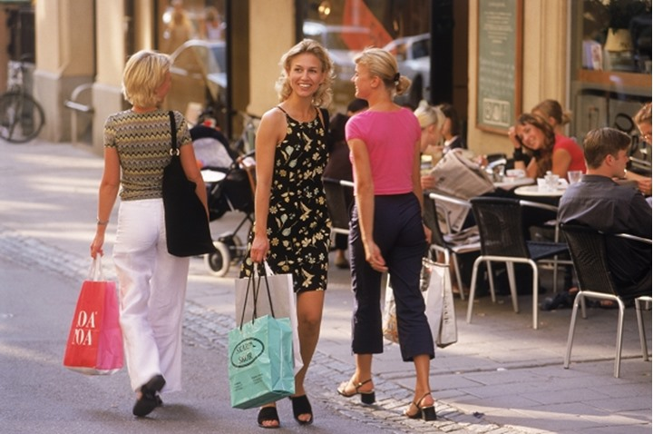 Three Swedish women with shopping bags on Stockholm street in summer