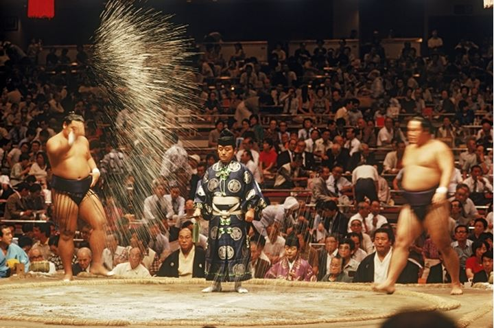 Pre fight sumo wrestling ceremony of tossing salt into ring or dohyo