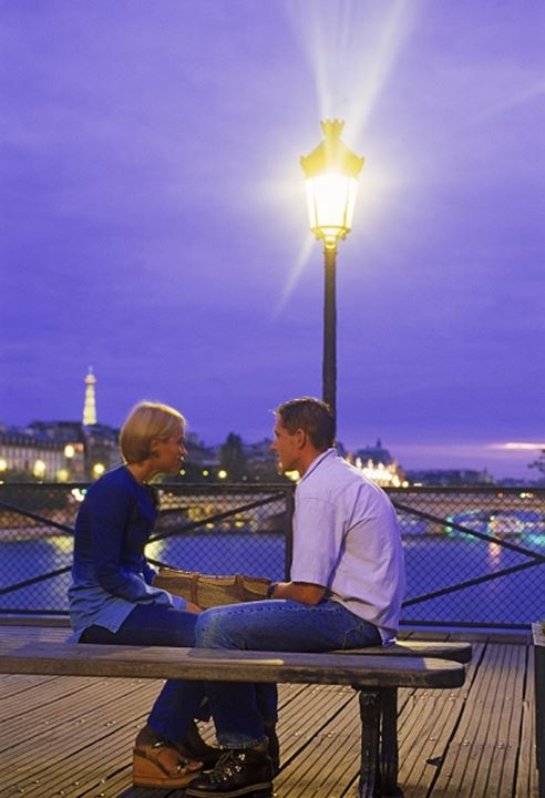 Young couple on Pont des Arts at night in Paris