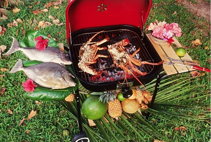 Barbequeing fresh fish and lobsters on backyard grill