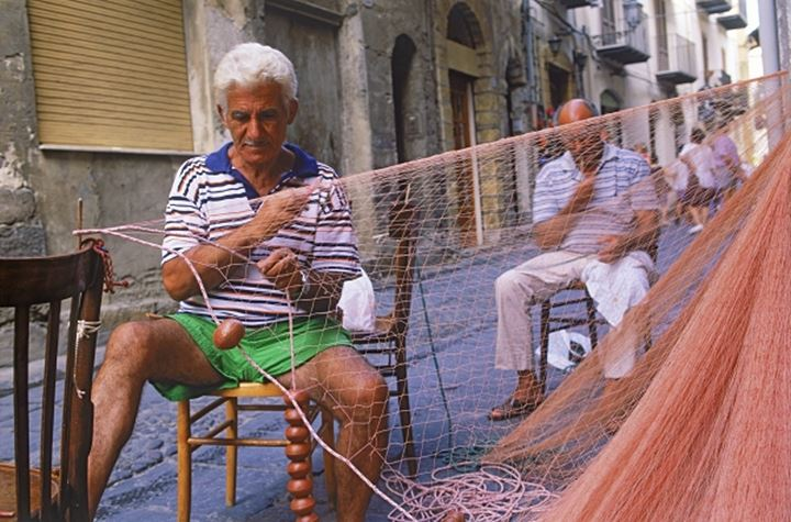 Men repairing fish nets in village of Cefalu on Sicily