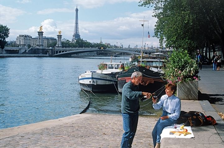 Couple having picnic on River Seine with Eiffel Tower