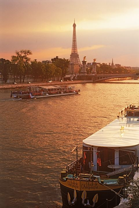 Sightseeing boat and houseboat on River Seine with Eiffel Tower