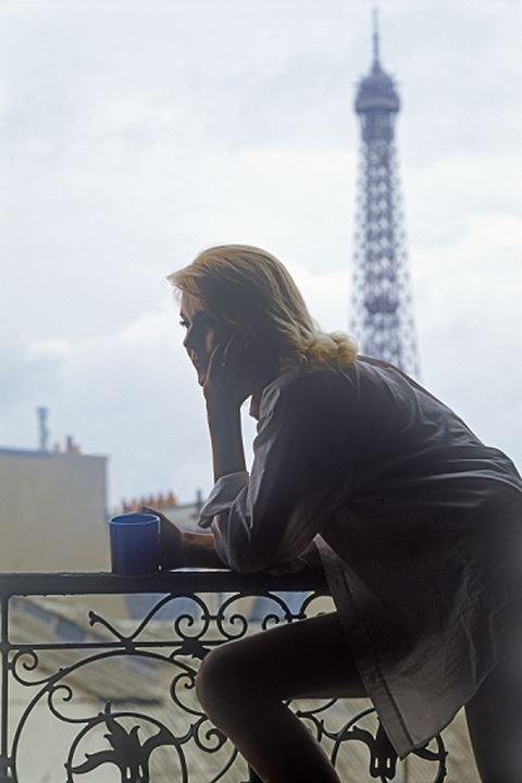 Woman in Paris apartment holding coffee cup with Eiffel Tower