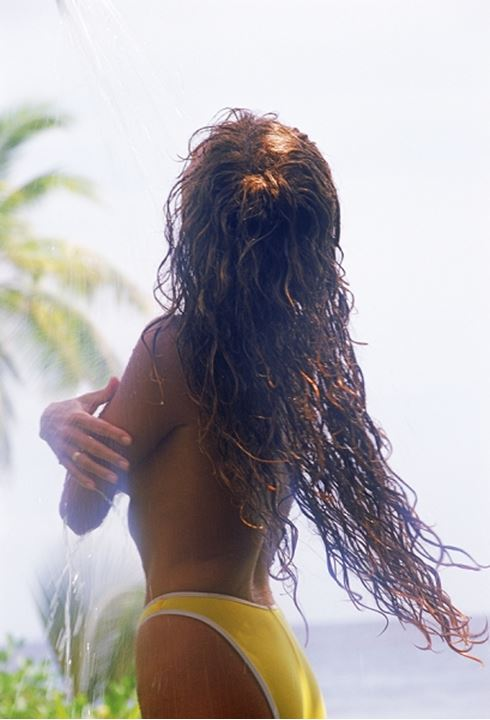 Woman with long red hair in outdoor shower
