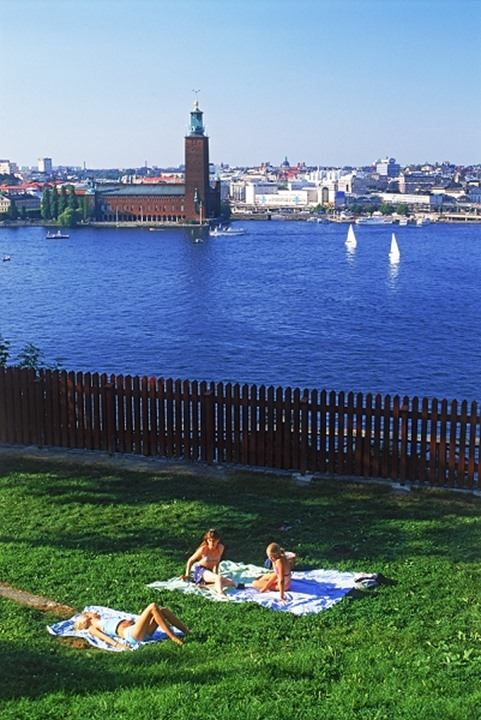 Summer picnic and sailboats on Riddarfjarden with City Hall in Stockholm
