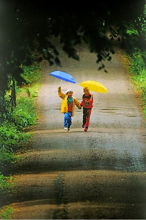 Boy and girl running on country road in the rain holding umbrellas