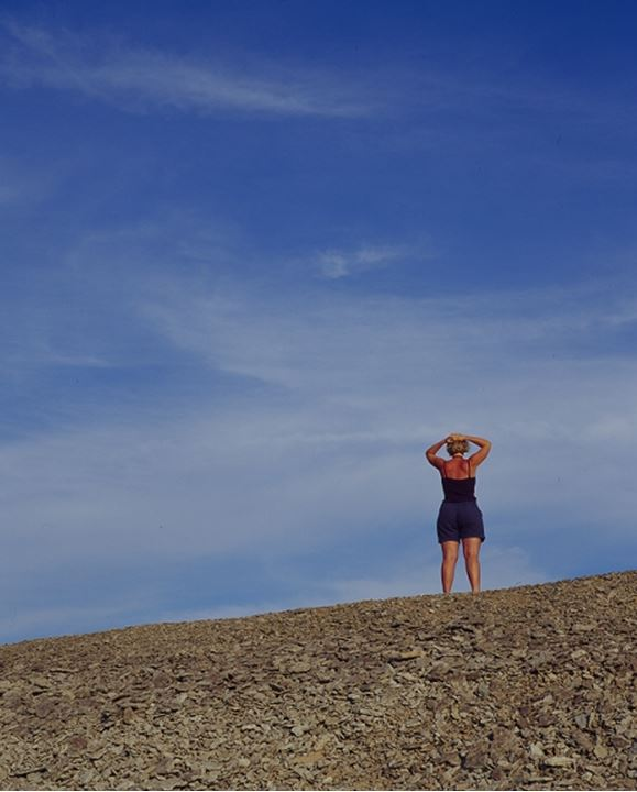 A woman on vacation standing upon a hill