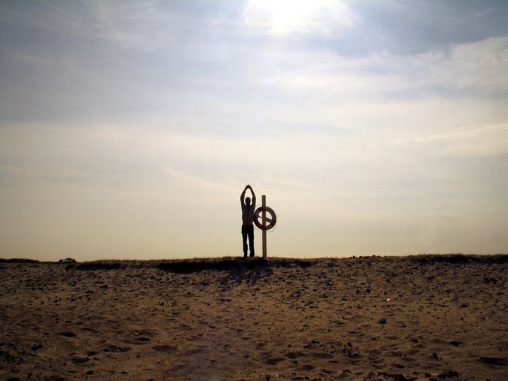 A man standing by a life buoy on a beach and doing exercise