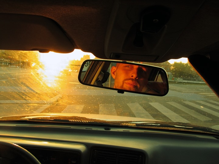 Reflection in the rear view mirror of a man driving a car in strong sunlight