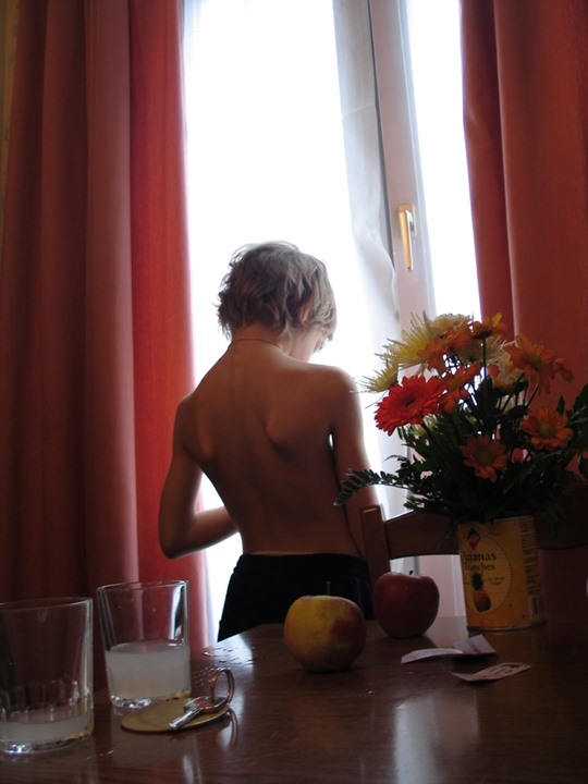 A still-life against a half naked child standing by a window in a hotel room, Paris