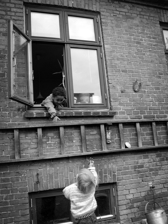 Two boys reaching for each other, one outdoors and another in a window
