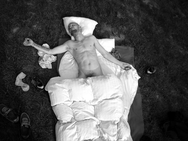 Nude man sleeping outdoors
