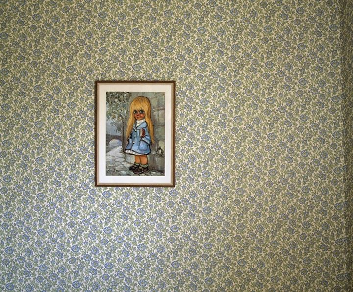 A picture hanging on a wallpapered wall