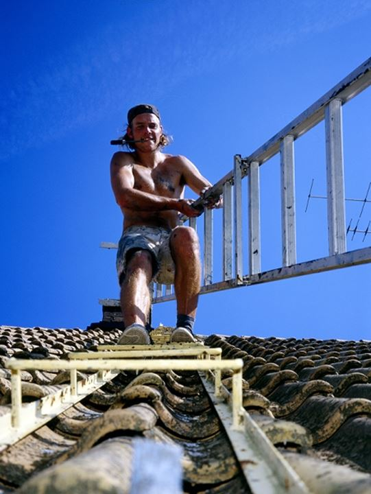 A man with a ladder on a roof