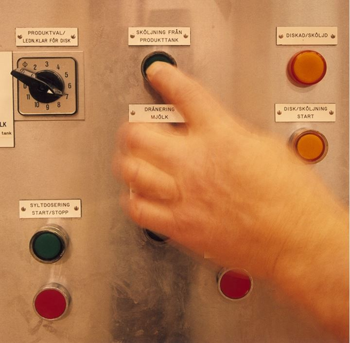 Close-up of a person's hand using a control panel
