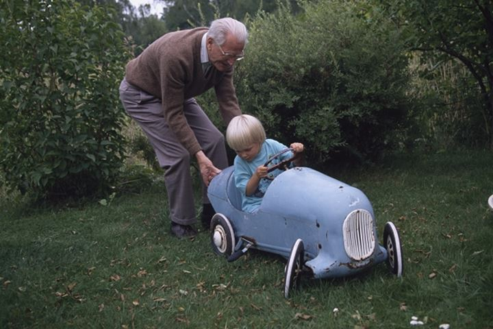 A grandfather pushing his grandson in a toy car