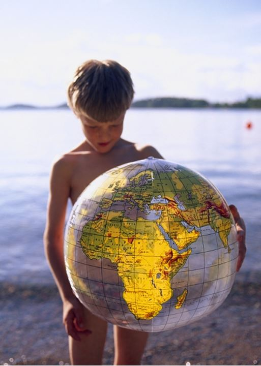 A boy holding a beach ball with the world globe printed on it