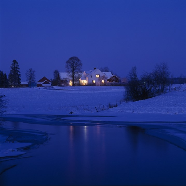 A lit up house at night in winter, Sweden