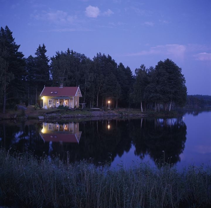 Reflection of a house in water at night, Lake Viken, Gota Canal, Vastergotland, Sweden